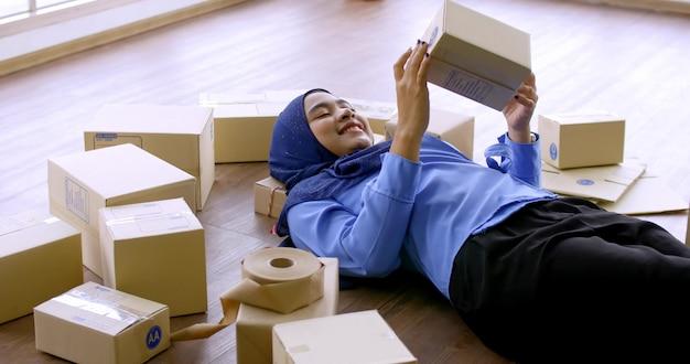 Mulher feliz comerciante muçulmano segurando a caixa de encomendas no escritório.