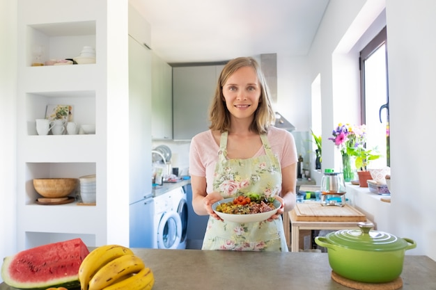 Mulher feliz cozinhando em casa, mantendo a dieta saudável, segurando a tigela de prato de vegetais caseiros, sorrindo para a câmera. vista frontal. conceito de alimentação saudável