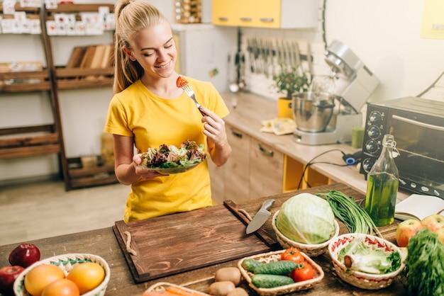Mulher feliz cozinhar salada na cozinha, preparação de alimentos saudáveis bio. dieta vegetariana, vegetais frescos e frutas na mesa de madeira