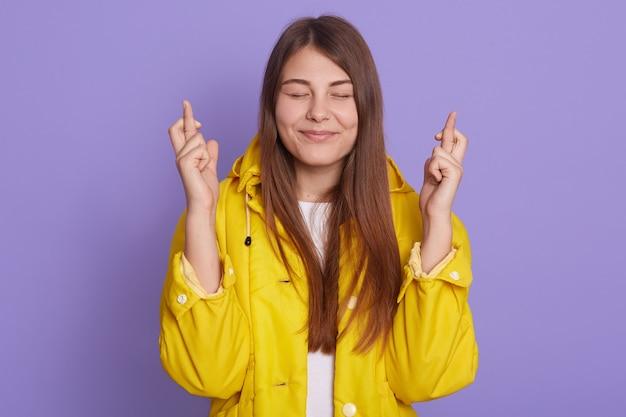 Mulher feliz cruza os dedos para dar sorte, usa jaqueta amarela, posando isolada sobre fundo lilás, mantém os olhos fechados e sorri, deseja algo ótimo.