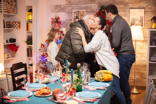 Mulher feliz cumprimentando o sogro para o jantar de natal em família.