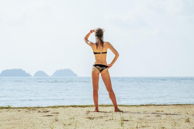 Mulher feliz curtindo a praia no verão. modelo de biquíni lindo relaxando na viagem