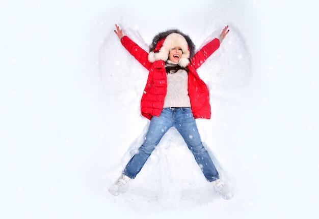 Mulher feliz curtindo a primeira neve, deitada na neve e fazendo anjo de neve
