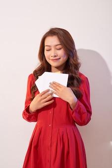 Mulher feliz curtindo cartão, lendo com prazer uma carta de amor, celebrando o dia dos namorados em casa