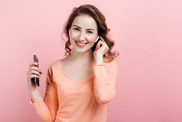 Mulher feliz curtindo música em airpods com parede rosa