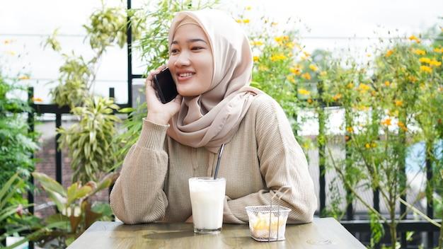 Mulher feliz da ásia hijab usando telefone inteligente e ligando, sentada em um café