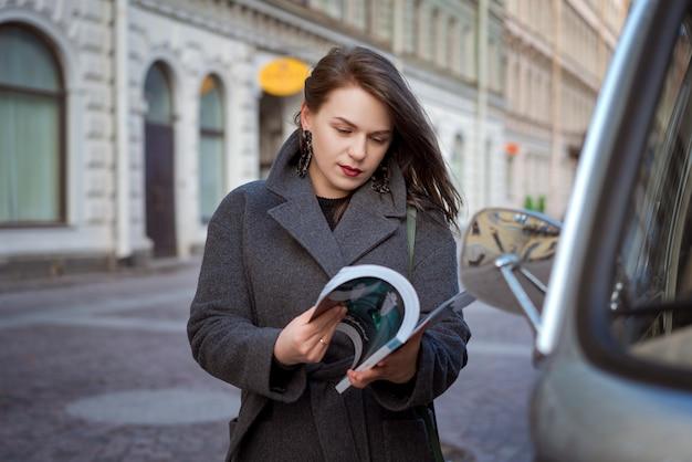 Mulher feliz da moda que lê uma revista em uma rua da cidade