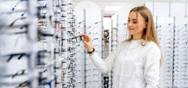 Mulher feliz da oculista optometrista parada com muitos óculos na ótica