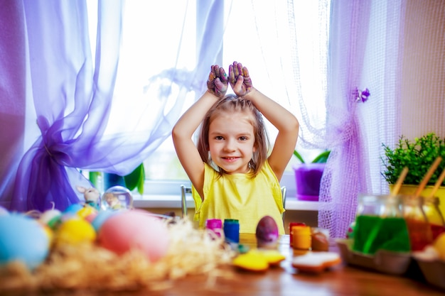 Mulher feliz da páscoa nas orelhas do coelho que pintam ovos, criança pequena em casa. feriado de primavera