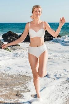 Mulher feliz de biquíni na praia em seu retrato de corpo inteiro de férias