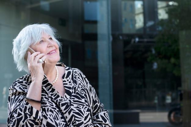 Mulher feliz de cabelos brancos falando ao celular na cidade