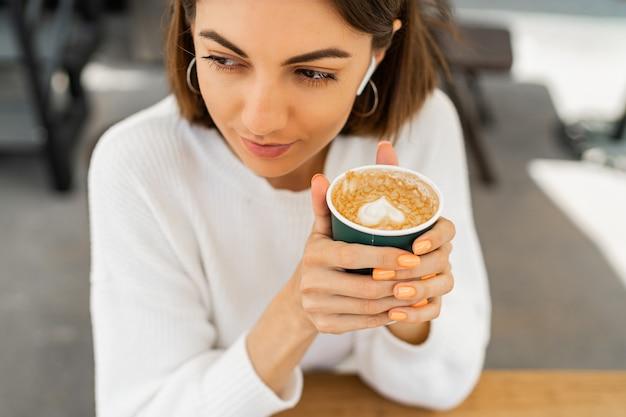 Mulher feliz de cabelos curtos saboreando capuccino em um café, vestindo um suéter branco aconchegante