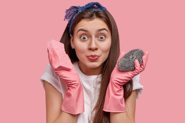 Mulher feliz de cabelos escuros se preocupa com a higiene e higiene, usa luvas de borracha, segura dois esfregões nas mãos, se prepara para limpar o banheiro imundo, usa camiseta branca