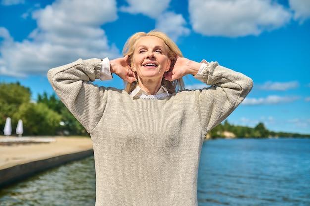 Mulher feliz de mãos dadas atrás da cabeça perto do mar