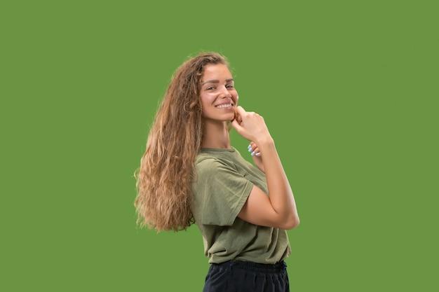 Mulher feliz, de pé e sorrindo contra verde