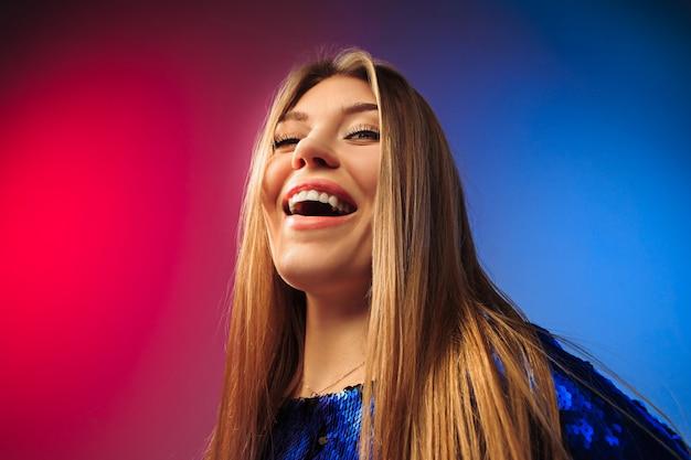 Mulher feliz, de pé, sorrindo no estúdio colorido.