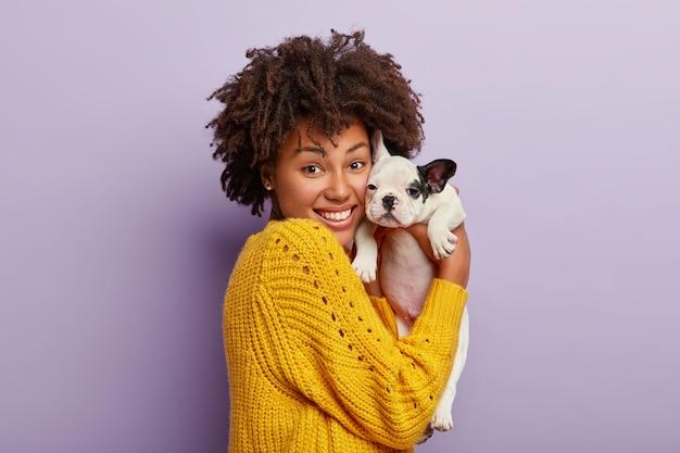 Mulher feliz de pele escura segura com ternura seu cachorrinho bulldog, faz retrato em estúdio