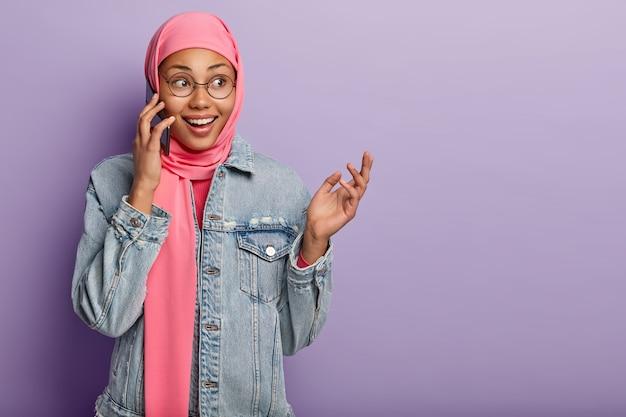 Mulher feliz, de pele escura, tem visões religiosas islâmicas, fala ao celular e levanta a mão