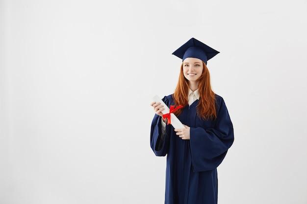 Mulher feliz de pós-graduação gengibre no boné e manto sorrindo segurando o diploma.