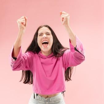 Mulher feliz de sucesso vitorioso comemorando ser um vencedor. imagem dinâmica do modelo feminino caucasiano no fundo rosa do estúdio.
