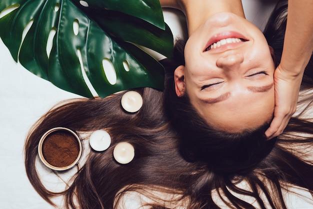 Mulher feliz deitada após um tratamento de spa em um fundo branco