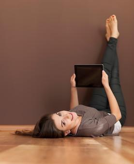 Mulher feliz deitada no chão com tablet digital