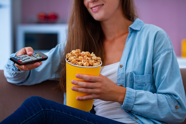 Mulher feliz, descansando no sofá e comendo pipoca de caramelo crocante durante assistir tv em casa. filme de pipoca