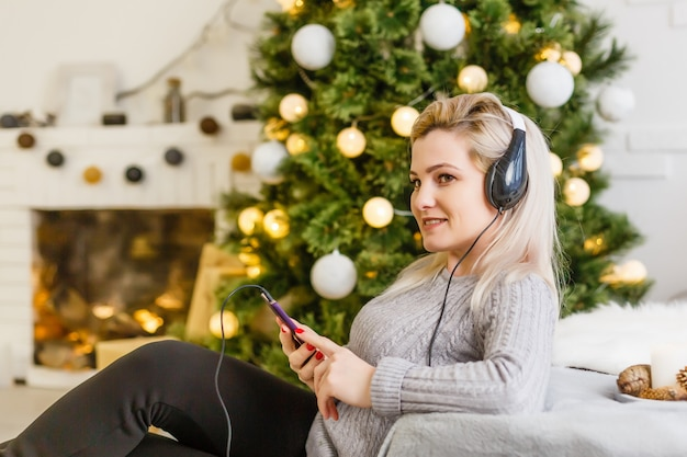 Mulher feliz, desfrutando de sua música no natal, relaxando em um sofá em frente à árvore com um sorriso radiante, apertando o celular no peito.