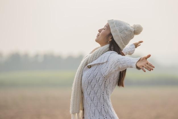 Mulher feliz desfrutando na natureza idílica, celebrando a liberdade e levantando os braços