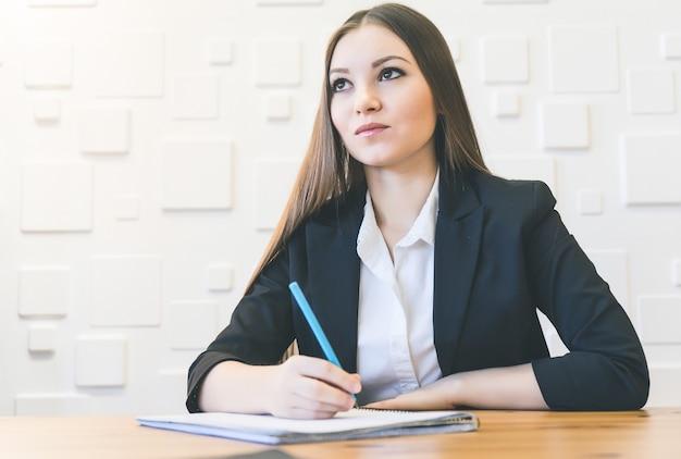 Mulher feliz do escritório com caneta escrevendo algo
