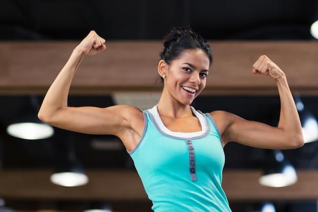 Mulher feliz do esporte mostrando o bíceps na academia