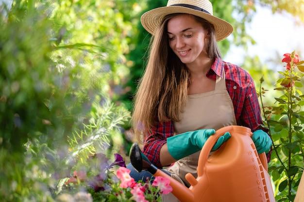 Mulher feliz do jardineiro em flores molhando do chapéu com o regador no jardim home. jardinagem e floricultura