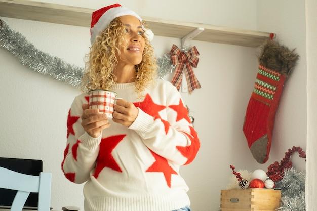 Mulher feliz e agradável sorria e aproveita a celebração e a decoração do natal em casa, sozinha, bebendo chá e usando chapéu de papai noel - pessoas felizes celebram a véspera de natal e os feriados de ano novo