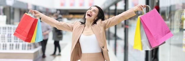 Mulher feliz e alegre com compras em shopping center