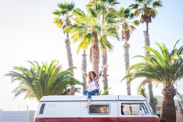 Mulher feliz e alegre de meia-idade desfrutando de uma viagem com uma velha van vintage vermelha em um lugar tropical para férias ou estilo de vida com desejo de viajar