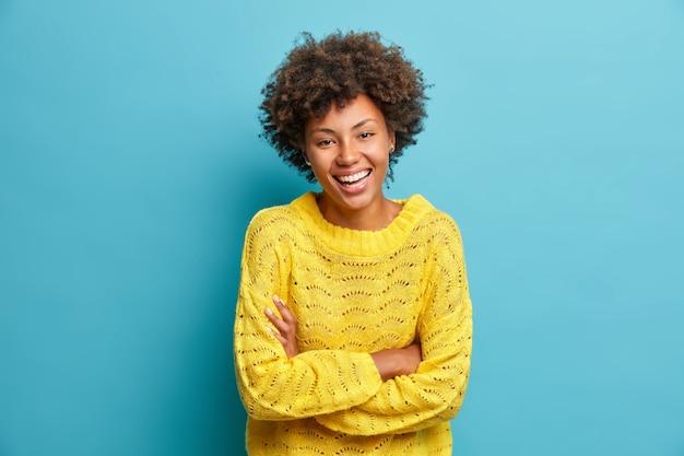Mulher feliz e alegre ri, mantém os braços cruzados e expressa emoções positivas, sorrisos de felicidade, vestida com um macacão casual isolado na parede azul, se diverte ou ouve uma piada engraçada