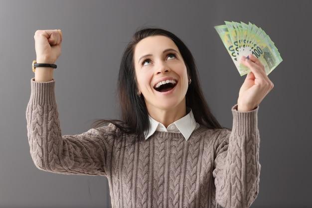 Mulher feliz e alegre segura dinheiro nas mãos, investimento lucrativo do conceito de fundos