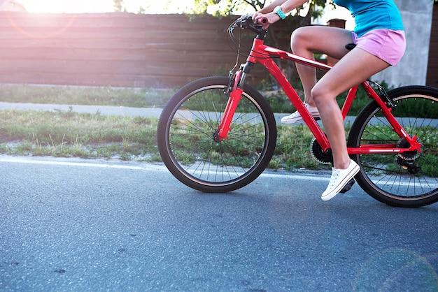 Mulher feliz e animada andando de bicicleta ao ar livre na estrada
