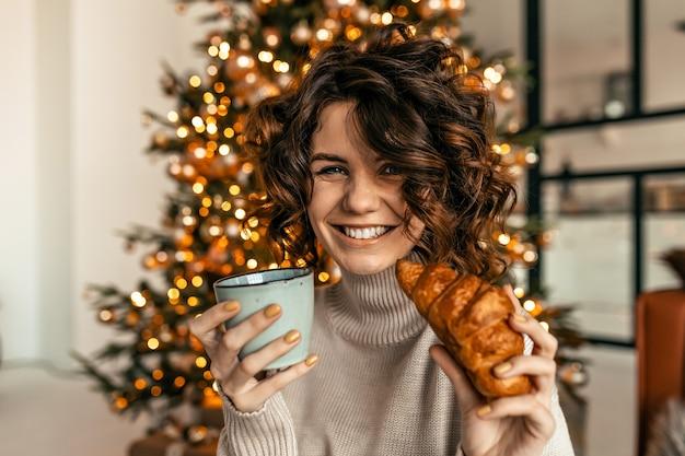 Mulher feliz e animada com cabelo curto e encaracolado posando com croissant e café da árvore de natal