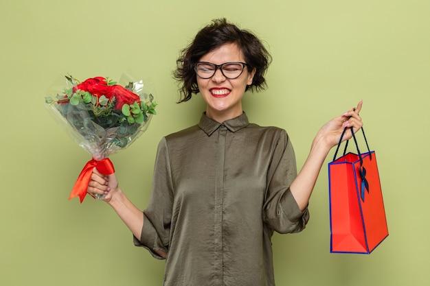 Mulher feliz e animada com cabelo curto segurando um buquê de flores e um saco de papel com presentes sorrindo alegremente
