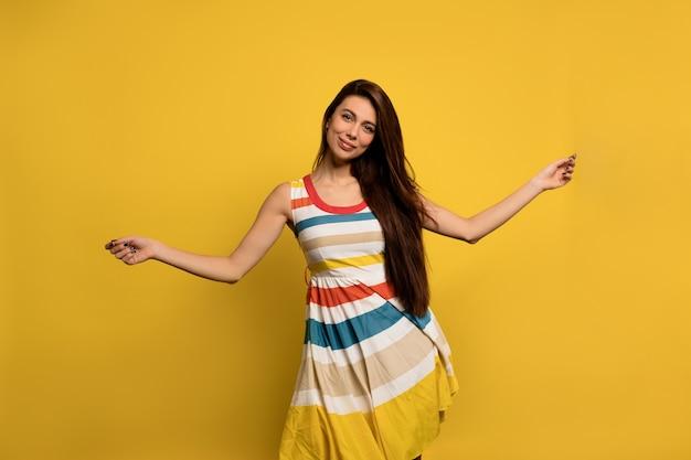Mulher feliz e animada com longos cabelos escuros em vestido de verão listrado brilhante se diverte e dança emoções felizes de mulher europeia.