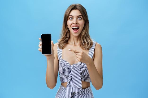 Mulher feliz e animada com os dentes separados finalmente comprou um smartphone novo, segurando o dispositivo na mão, apontando para a tela do celular, mostrando um aplicativo legal sorrindo amplamente de alegria contra a parede azul