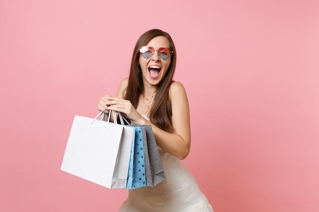 Mulher feliz e animada em um vestido branco, óculos em forma de coração gritando, segurando sacolas de pacotes coloridos com compras