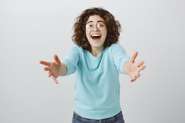 Mulher feliz e animada estendendo as mãos para frente para segurar ou pegar algo