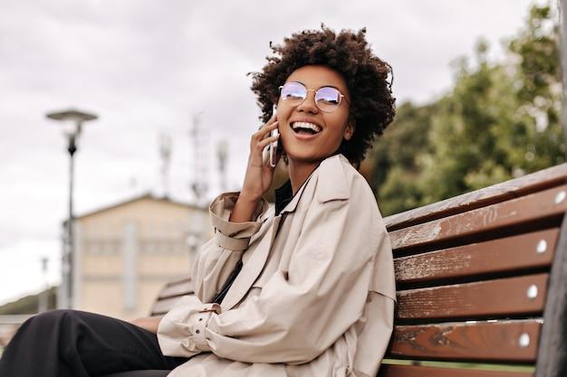 Mulher feliz e animada morena encaracolada em gabardine bege e óculos, ri, fala ao telefone e se senta no banco de madeira do lado de fora