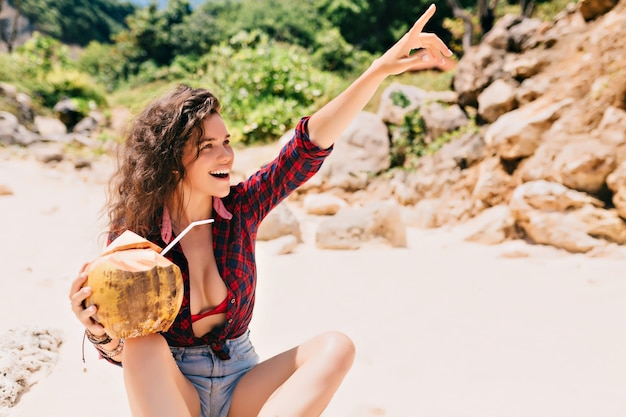 Mulher feliz e animada vestida de shorts e camisa brilhante sentada na praia com coquetel de coco e apontando para o lado