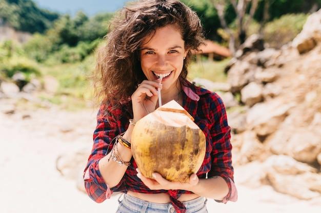 Mulher feliz e animada vestida de shorts e camisa brilhante sentada na praia com coquetel de coco