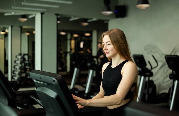 Mulher feliz e atlética correndo em uma esteira em uma academia