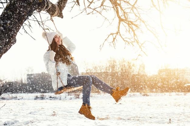 Mulher feliz e balanço de corda na paisagem de inverno