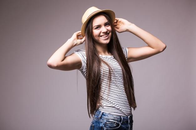 Mulher feliz e brincalhona usando chapéu de palha de verão olhando para o lado por cima do ombro